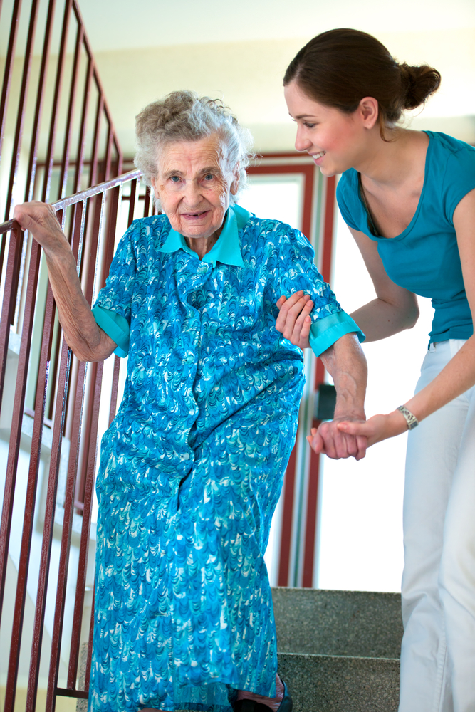 Young woman helping older woman down stairs