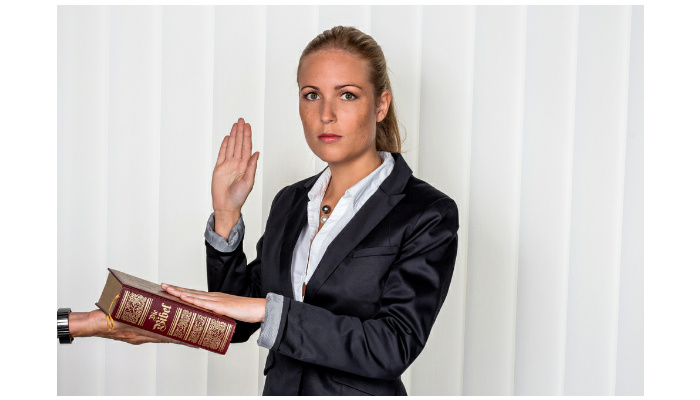 A woman says as a witness in court in a lawsuit, will be sworn in and swears on the bible. Shutterstock Image ID 280831940. Copyright, Lisa S.